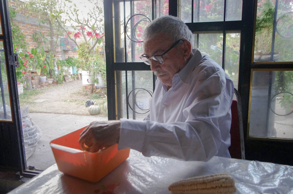 Tio Miguel, shelling dry corn for his chickens